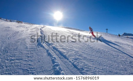 Snowboarder going down the slope in Goldeck, Austria. Perfectly groomed slopes. Crispy snow is thrown up under the pressure of the ski. A girl wears pink trousers, colorful jacket and protection helm #1576896019