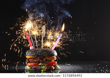 Burger sandwich with black bun, sparklers and candle for holiday. Beautifully designed for the holiday sandwich. Copy space. Photo on black background. #1576896493