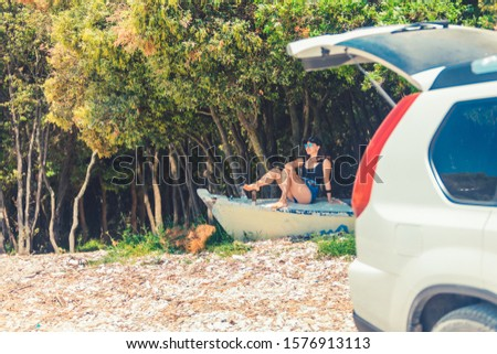 young woman sitting on boat at beach near car