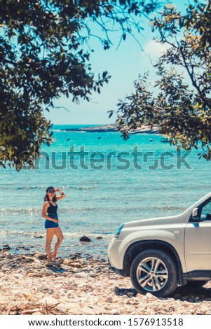 woman standing at the beach car travel concept