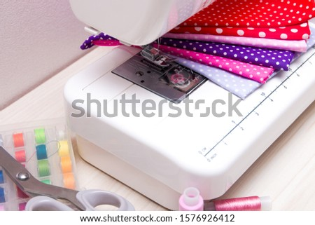 sewing machine on the table, fabrics for girls, scissors and spools of thread #1576926412