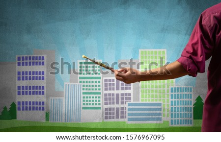 Close up artist hand holding paintbrush. Painter in shirt standing on background colorful picture of city. Modern cityscape with high skyscrapers artwork. Creative hobby and artistic occupation. #1576967095