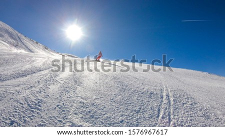 Snowboarder going down the slope in Goldeck, Austria. Perfectly groomed slopes. Crispy snow is thrown up under the pressure of the ski. A girl wears pink trousers, colorful jacket and protection helm #1576967617
