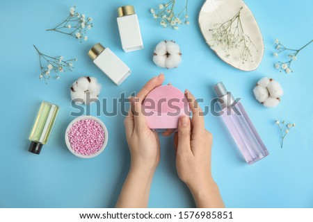 Woman with face cleansing brush on light blue background, top view. Cosmetic accessory