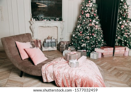New Year's decor idea for a living room with gifts under a Christmas tree. Delicate pink and white balls and beads on fir tree branches, a pile of light gift boxes #1577032459