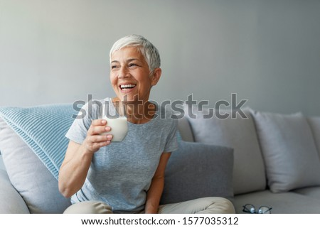 Senior woman's hands holding a glass of milk. Happy senior woman having fun while drinking milk at home. Senior Woman drinking a glass of milk to maintain her wellbeing. #1577035312