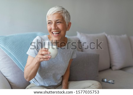 Senior woman's hands holding a glass of milk. Happy senior woman having fun while drinking milk at home. Senior Woman drinking a glass of milk to maintain her wellbeing. #1577035753