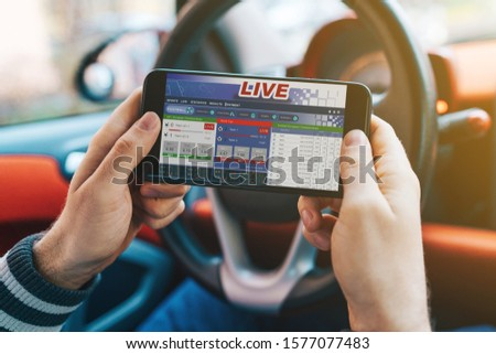 Close up cropped shot of man hand holding mobile phone with bookmaker;s website on its screen. Male gambler betting online using mobile application white sitting in a car. #1577077483