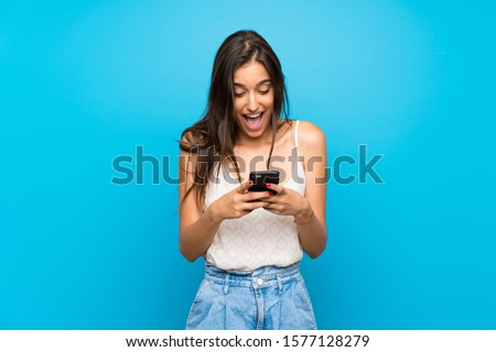 Young woman over isolated blue background surprised and sending a message