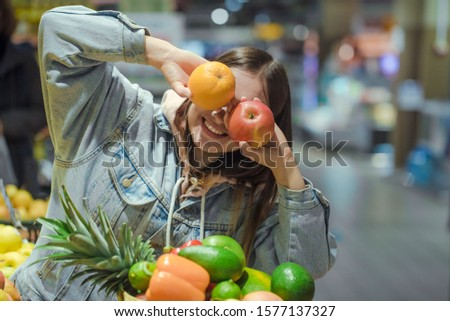 Young cheerful woman with fruit in her hands in the supermarket . Health food. Healthy food, organic products. #1577137327