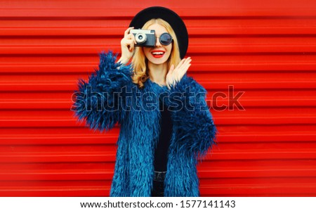 Portrait stylish surprised woman with retro camera taking picture wearing blue faux fur coat, round hat and sunglasses over colorful red wall background #1577141143