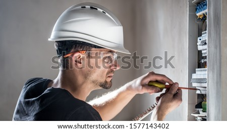 Man, an electrical technician working in a switchboard with fuses. Installation and connection of electrical equipment. Professional with tools in hand. concept of complex work, space for text. #1577143402