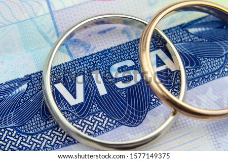 Macro photo of US entry visa sticker in a passport and a couple of rings. Conceptual photo for immigration. Selective focus.  Royalty-Free Stock Photo #1577149375