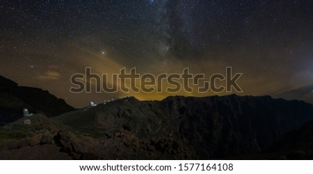 Long exposure. Giant volcano with astronomical Observatory under the bright stars. Milky Way galaxy on the darky orange purple mountain sky. Towers and domes of telescopes are aimed at celestial. #1577164108