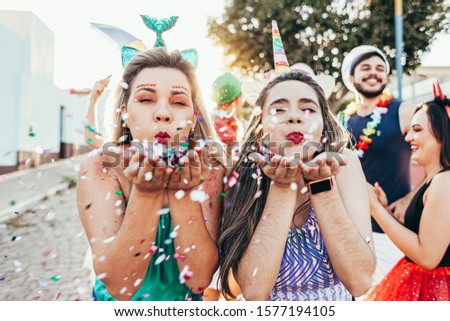 Brazilian Carnival. Young women in costume enjoying the carnival party blowing confetti #1577194105