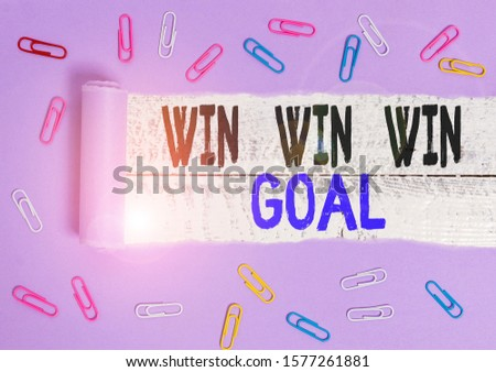 Handwriting text Win Win Win Goal. Concept meaning Approach that aims to satisfy all parties involved Paper clip and torn cardboard placed above a wooden classic table backdrop. #1577261881