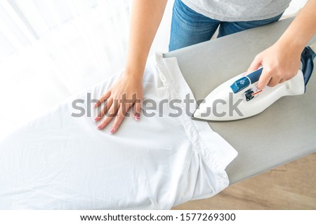 Female hands ironing white shirt collar on ironing board, view from above #1577269300