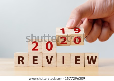 2020 review concept. Hand flip wood cube change year 2019 to 2020 and the word REVIEW on wooden block on wood table Royalty-Free Stock Photo #1577296309