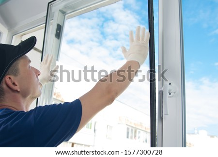 master in protective gloves, changing a double-glazed window in a plastic window, side view, against the blue sky