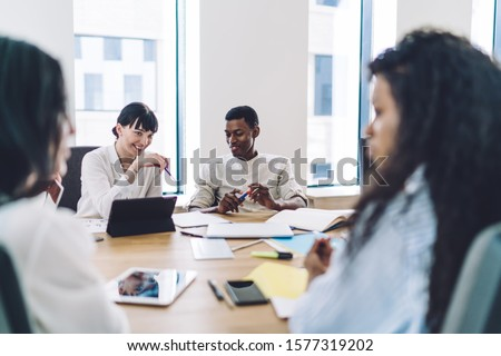Cheerful smart business people having brainstorming joyfully at meeting sitting at table with stationery and gadgets in workplace joking over ideas #1577319202