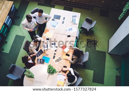 From above executives in formal wear sitting at meeting table with documents and laptop having conversation discussing work plan in corporation #1577327824