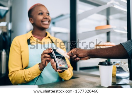 African American cheerful lady with short hairstyle in apron taking payment for order from black crop client using credit card in coffee shop. Terminal machine with wireless contactless payment