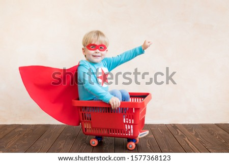 Happy superhero child playing at home. Super hero kid having fun. Success, creative and start up concept #1577368123