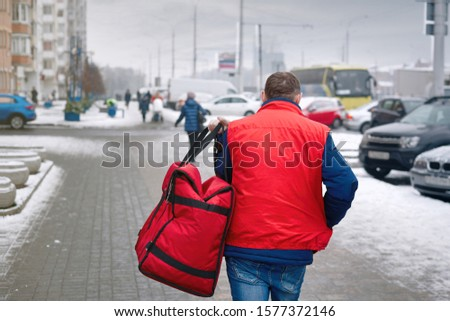 Man is delivering food with red thermal backpack. Pizza delivery - courier goes and carries isothermal bag in left hand. Fast delivery service from favorite restaurants in any weather around the clock #1577372146