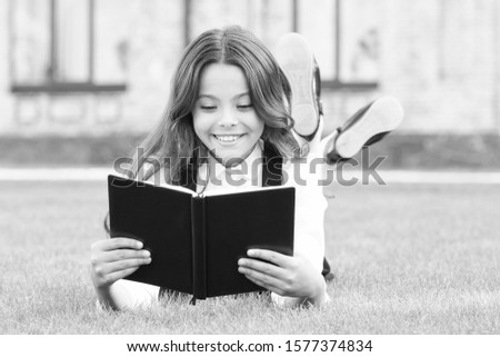 Knowledge is more than information. Happy small girl read book on green grass. Adorable little schoolchild get knowledge from reading. Knowledge day or September 1. Test your school knowledge. #1577374834