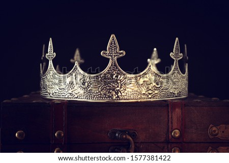 low key image of beautiful queen/king crown over wooden table. vintage filtered. fantasy medieval period Royalty-Free Stock Photo #1577381422