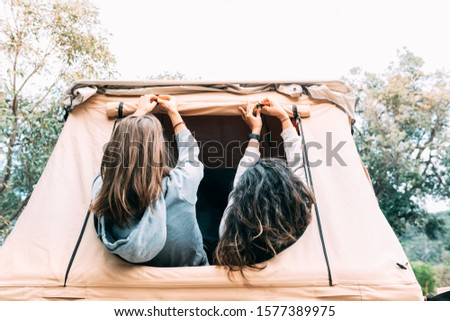 Two camper girls who love nature set up their tent from inside. How to set up a tent is not always an easy task. Camping experience is an advantage. Horizontal picture. Blank space to type.