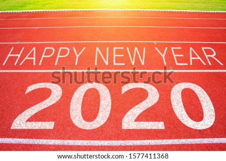 White lines of stadium and texture of running racetrack red rubber racetracks with 2020 Happy New Year text,During Christmas and New Year. #1577411368