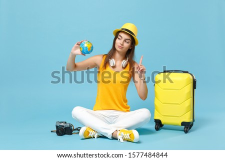 Traveler tourist woman in yellow casual clothes hat with suitcase photo camera isolated on blue background. Female passenger traveling abroad to travel on weekends getaway. Air flight journey concept #1577484844