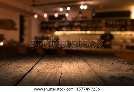 blur bokeh reflection light on table in pub or bar club and restaurant Christmas party and celebrate at dark night for display product in brown tone background #1577499256