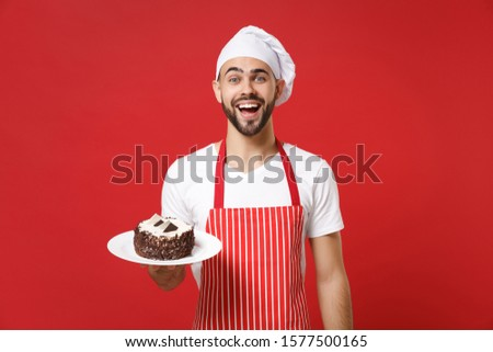 Excited young bearded male chef cook or baker man in striped apron white t-shirt toque chefs hat posing isolated on red background. Cooking food concept. Mock up copy space. Holding plate with cake #1577500165