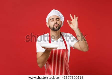 Chef cook or baker man in striped apron toque chefs hat isolated on red background. Cooking food concept. Mock up copy space. Hold empty blank plate with place for food making okay taste delight sign #1577500198
