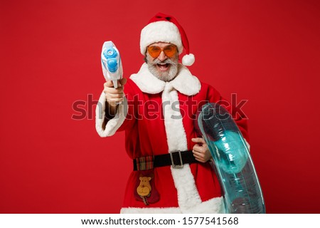 Elderly gray-haired mustache bearded Santa man in Christmas hat sunglasses posing isolated on red background. New Year 2020 celebration concept. Mock up copy space. Hold inflatable ring toy water gun #1577541568