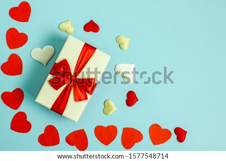 Valentines day flat lay copy space. On a blue background a gift box and a red bow, red paper hearts, hearts made of white fabric and red satin. In the center is a place for text. #1577548714