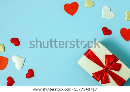 Valentines day flat lay copy space. On a blue background a gift box and a red bow, red paper hearts, hearts made of white fabric and red satin. In the center is a place for text. #1577548717