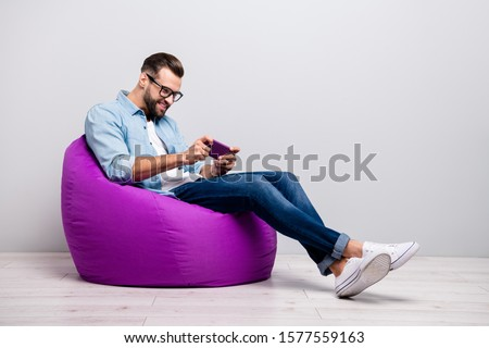 Full length profile photo of positive guy sitting comfy violet armchair holding telephone playing new game wear specs casual denim outfit isolated grey color background