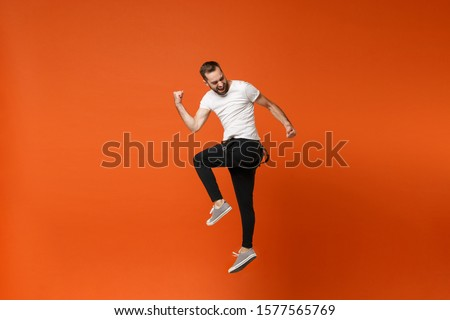 Cheerful young man in casual white t-shirt posing isolated on bright orange wall background studio portrait. People lifestyle concept. Mock up copy space. Having fun, jumping, doing winner gesture #1577565769
