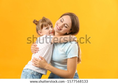 Portrait of happy mother and daughter on color background #1577568133