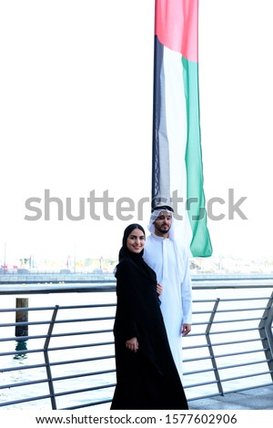 Arab couples standing beside United Arab Emirates Flag. Arabic woman in Abaya Hijab and man in Kandoora looking at the camera with happy face in UAE #1577602906