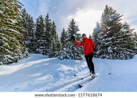 Woman cross country skiing on a sunny winter morning in Swiss Alps, Thyon, les collones, Valaise canton. Royalty-Free Stock Photo #1577618674
