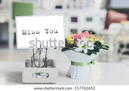 Postcard with message miss you and fresh flowers on table