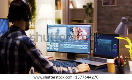 Film maker pointing at the monitor in home office while working on post production for a movie. Video editor wearing headphones. #1577644270