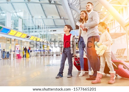 Family with two children on vacation at the airport or train station #1577665201