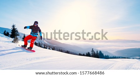 Bright Young Snowboarder Riding Red Snowboard in the Mountains at Sunny Day. Snowboarding and Winter Sports #1577668486