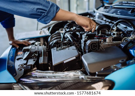 Mechanic man examining and maintenance to customer the engine a vehicle car hood, Safety inspection test engine before customer drive on a long journey, transportation repair service center #1577681674