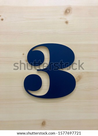 Navy blue raised number 3 isolated on a wood grain background with a drop shadow